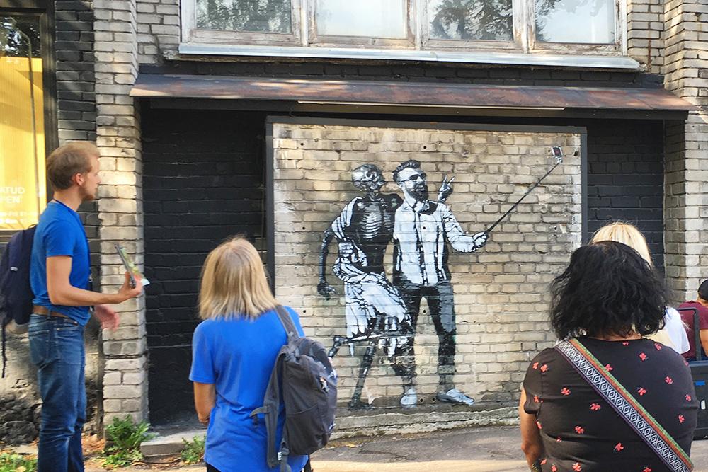 В Теллискиви проводят экскурсии. Этот гид рассказывает про граффити хипстера со смертью