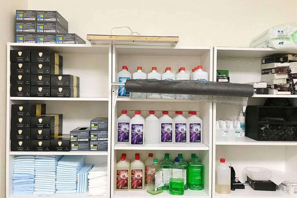 В мастерской есть отдельное помещение длястерилизации инструментов и хранения расходных материалов. Слева в черных упаковках лежат одноразовые перчатки, под ними — одноразовые пеленки длязаматывания свежей татуировки после сеанса. В центре — жидкости длязамачивания железных инструментов