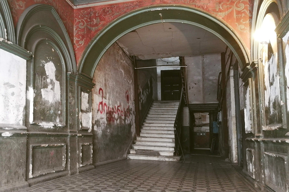 Это подъезд особняка 19 века на улице Асатиани. На потолке — фреска, а на стене — граффити. Но по местным меркам тут чисто