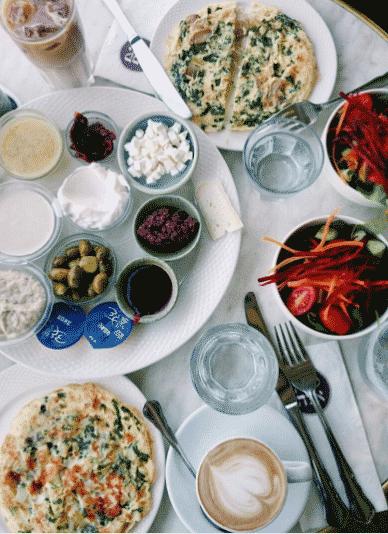 Типичный израильский завтрак: омлет, овощной салат и набор закусок — оливки, сыр булгарит, тхина, баклажан с тхиной, творожный сыр, масло, джем, кофе