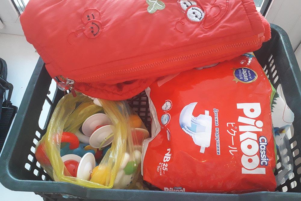 Все игрушки и одежду приношу в мечеть в таком виде. В корзине упаковка подгузников, погремушки в полиэтиленовом пакете и куртка дляноворожденного