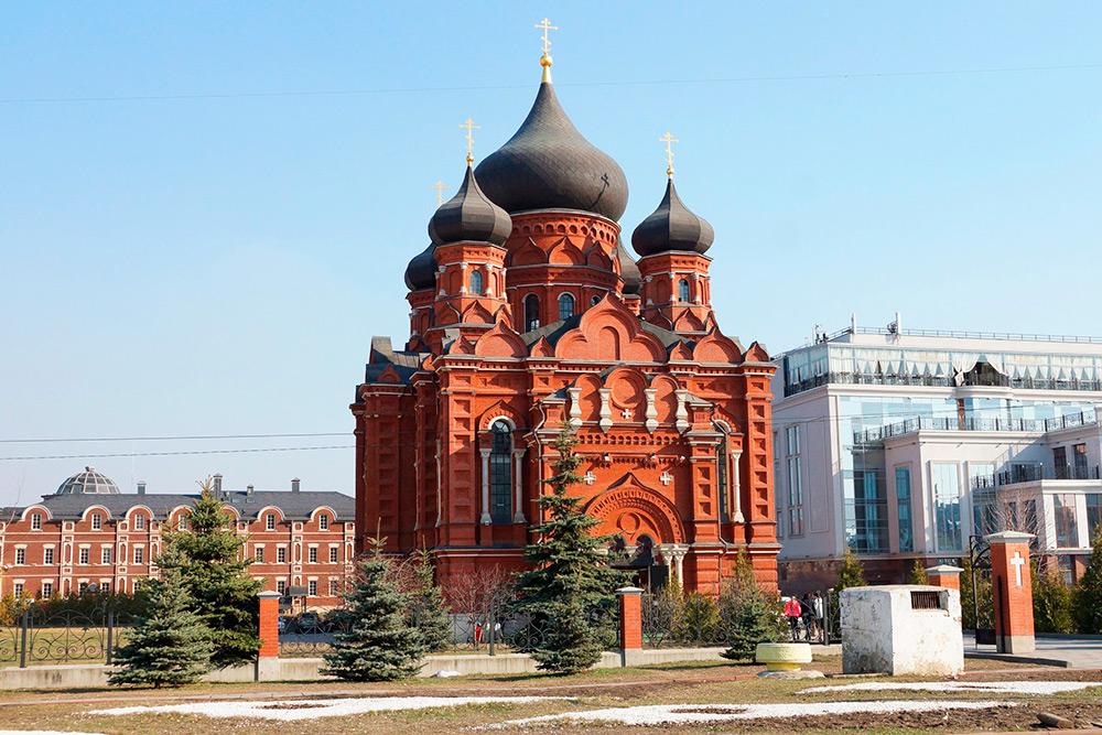 Собор выглядит впечатляюще по сравнению с современным зданием Гостиного двора справа