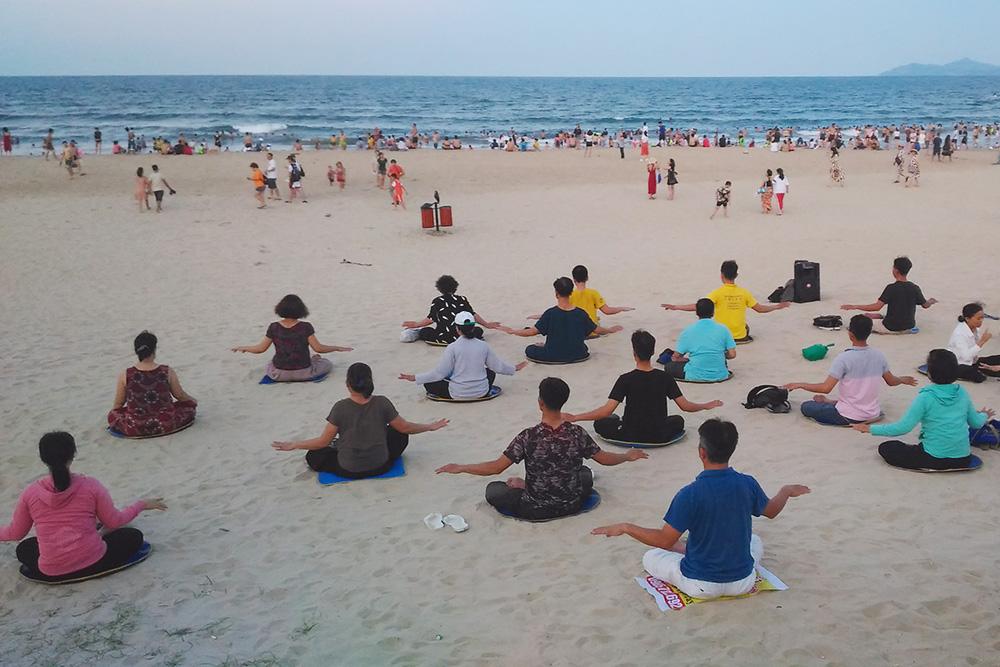 Вьетнамцы на закате занимаются йогой на пляже, это бесплатная группа для всех желающих