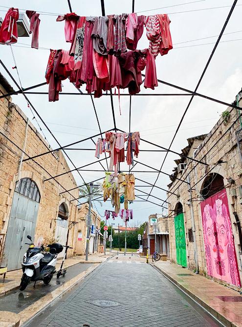 Улочка в старом районе Яффа, где одежда на перекладинах висит как арт-объект