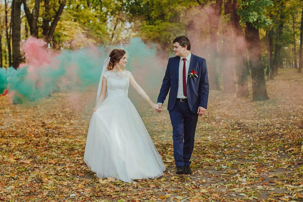 Типичная фотография прогулки — молодожены смотрят друг на друга, в их взглядах любовь и счастье. Свидетель стоит за кадром и пускает разноцветный дым