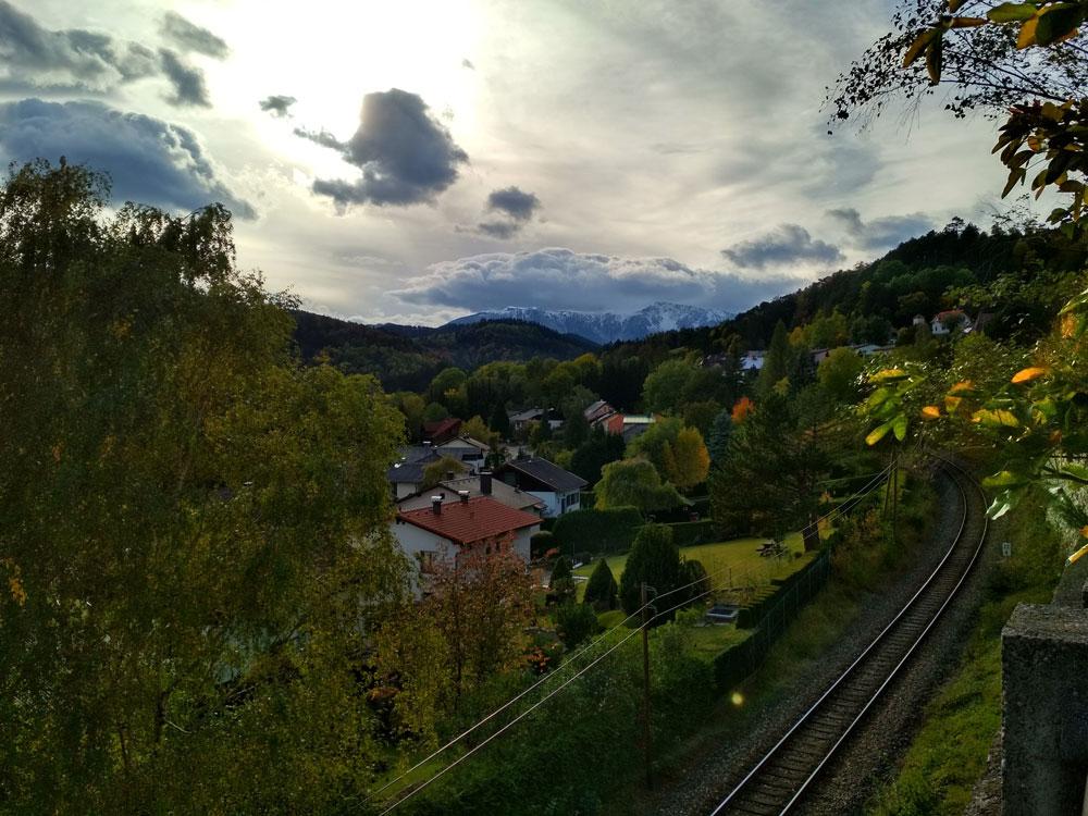 В Австрии мы исследовали окрестные горы и спускались в ущелья. Высокая снежная гора за деревней — это Альпы