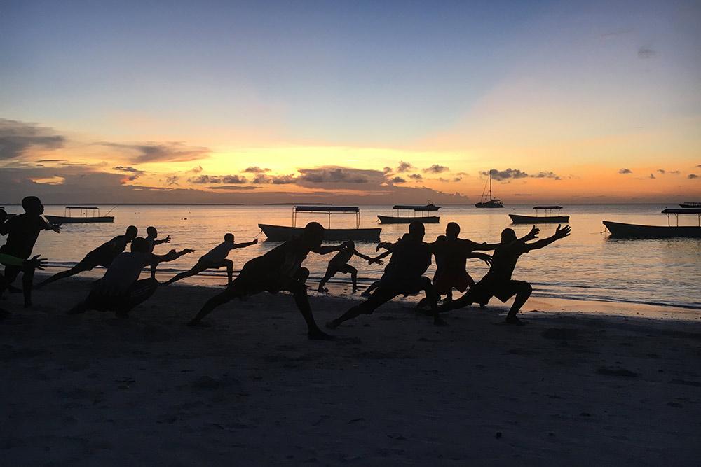 Вечером на Занзибаре местная молодежь занимается спортом на пляже, например гимнастикой или капоэйрой