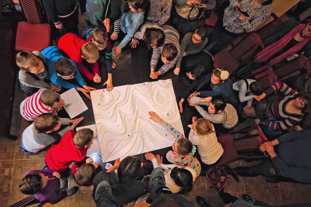 На фото занятие в детской библиотеке «Пионер» на Киевской. Дети окружили тот самый макет парка «Вулканы Камчатки», который оказался слишком громоздким для перевозки и неудобным для сборки в классе