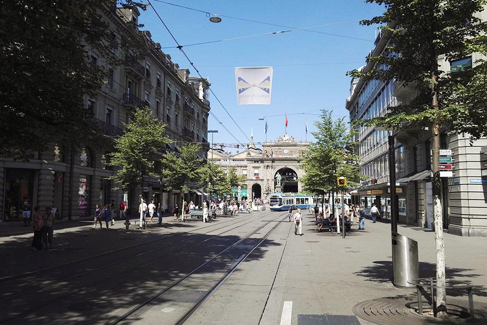 По улице медленно ездят бело-голубые трамваи и гуляют люди